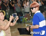 아줌마 팬이 SM타운 콘서트차 12일 오후 김포국제공항을 통해 일본 도쿄로 출국하는 슈퍼주니어 려욱을 바로 앞에서 핸드폰에 담고 있다.